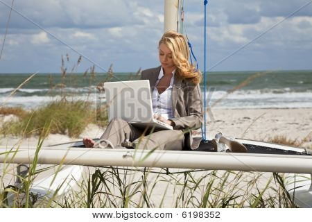 Beautiful Young Woman Using Laptop On Boat At The Beach