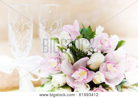 Two glasses of champagne and a beautiful tender festive wedding bouquet of flowers, buttercups and white lilac on a white painted wooden board. poster