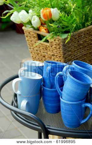 Blue cups and flower basket on a metal side table