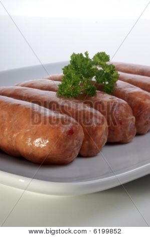 Organic Bramley Apple Sausages On A White Plate