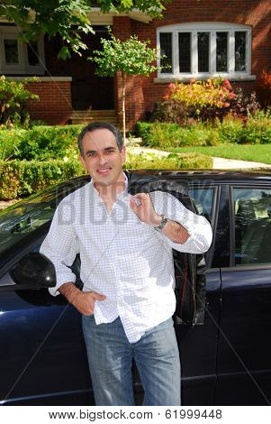 A man standing outside leaning on his car in front of his house