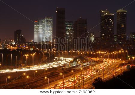 Cars, train, traffic flowing out of city.