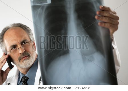 Doctor Looking At X-ray And Using Cell Phone