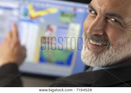 Businessman Smiling And Pointing To Computer Monitor