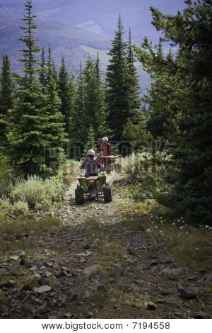 Two Teens Riding Atv Down Trail