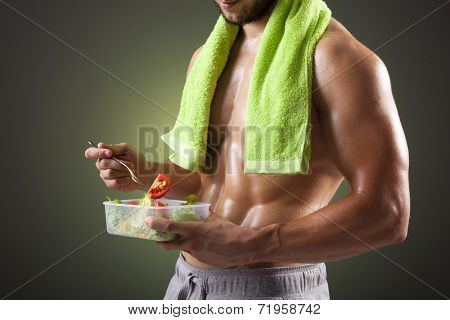Fitness man holding a bowl of fresh salad on black background