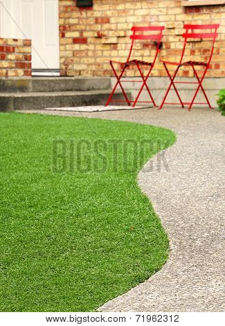Walk way with perfect grass landscaping with artificial grass in residential area