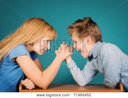 Son confronts his mother. Family, parents and children conflict concept. Woman and boy arm wrestling