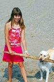 Young pretty girl playing with a dog on a sandy beach poster