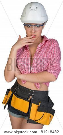 Woman in hard hat, protective glasses and tool belt