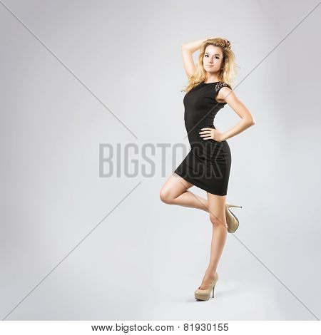 Beautiful Woman in Black Dress on Gray Background