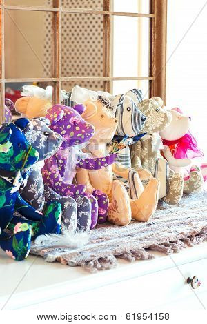 Many tilda textile teddy bear toys sitting in a row in workshop. Indoors. poster