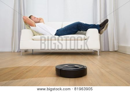 Robotic Vacuum Cleaner In Front Of Man Relaxing