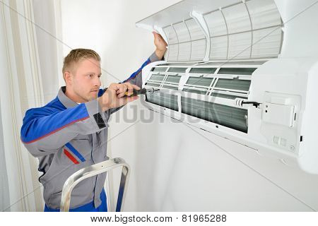 Portrait Of Male Electrician Repairing Air Conditioner Standing On Stepladder poster