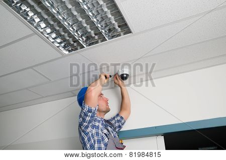 Close-up Of Male Technician Adjusting Cctv Camera On Ceiling poster