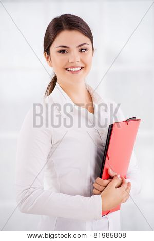 Beautiful young businesswoman cheerfully smiling, holding folders and looking at camera. Isolated on white background poster