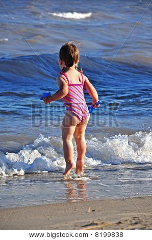 Little cute girl jumping in waves