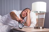 Man Irritated With Noise Snoozing Alarm Clock poster