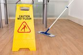 Close-up Of Wet Floor Sign And Mop On Hardwood Floor poster