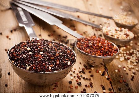 Mix of quinoa grain in metal measuring spoons