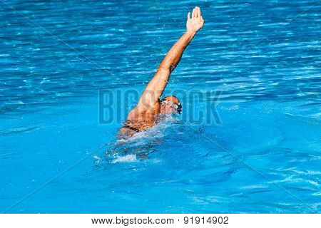 young man swim backstroke style in outdoor swimming pool, sunny summer day