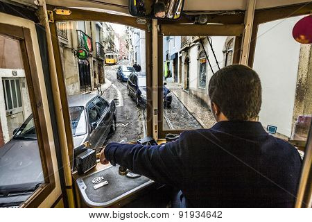 Tagged Tram Is Making Its Way Through A Narrow Stree