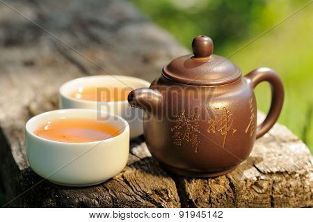 Two Cups Of Black Tea And Chinese Clay Teapot On Old Wooden Board