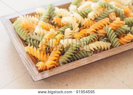 Raw Fusilli Pasta On Wooden Tray
