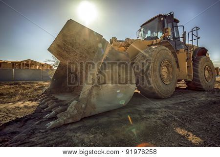 Heavy duty construction digger excavator equipment with sun flare.