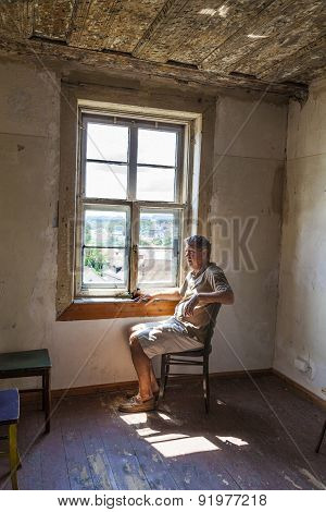 Man Sitting At The Window Of An Old House