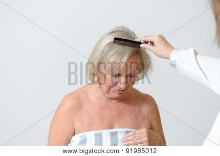 Elderly lady gets her hair combed maybe she lives in a home for old people and needs care poster