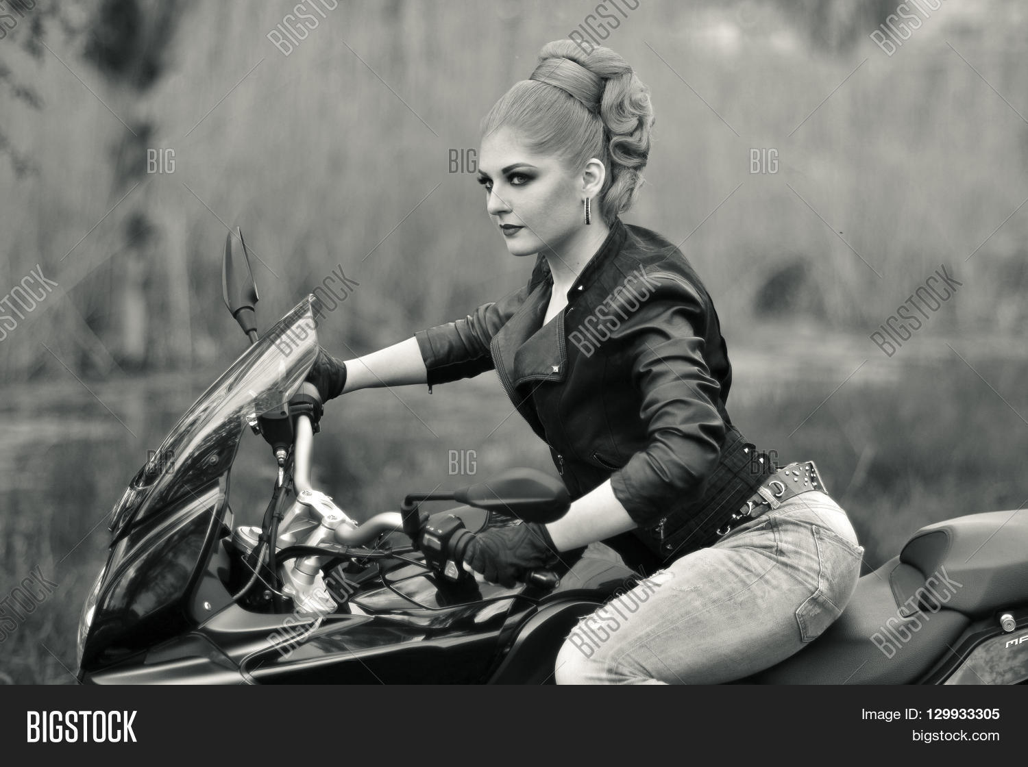 Black and white photo professional biker girl fast rider sitting on black