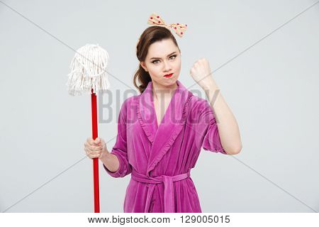 Mad irritated young woman with mop showing fist poster