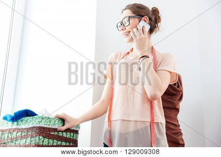 Happy charming young woman seamstress looking at the window and using smartphone in workshop