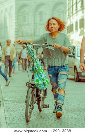 FLORENCE, ITALY - JUNE 12, 2015: Asian women walking next to her bycicle, a nice colored shopping bag hanging from bycicle.