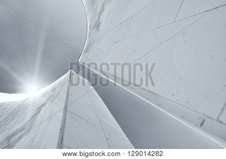 Perspective bottom view of semicircular walls in futuristic urban style. Architecture urban background with reflected lights. Modern architecture cityscape black and white tones applied.