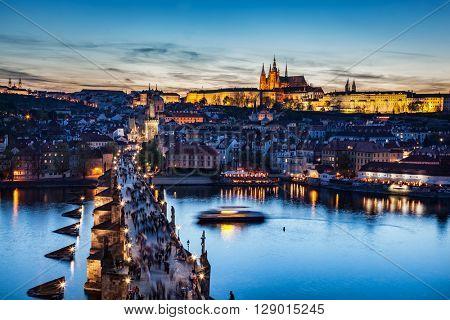Charles Bridge on Vltava river in Prague, Czech Republic at late sunset, night. View on Prague Castle, Hradcany