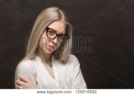 young skeptical woman in eyeglasses on black background with copyspace