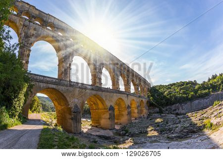 The bridge was built in Roman times on the river Gardon. Three-tiered aqueduct Pont du Gard - the highest in Europe. Provence, setting sun shines in sky