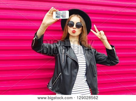 Fashion Pretty Woman Makes Self Portrait On Smartphone In Black Rock Style Over City Pink Background