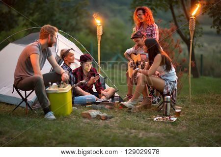 Socializing youngsters in front of tent with beer, guitar and drums at night