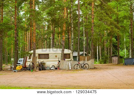Summer outdoor recreation Scandinavian vacation. Camping vans and bikes parked in a wooded campsite among pine trees. Finnish Gulf. Area for camp in woods. Hamina Finland Suomi