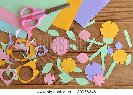 Paper flowers, paper sheets, scissors, paper scrap on a wooden table. Paper flower craft for kids. Children's art project.