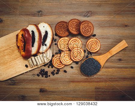 There are Pieces of Roll with Poppyseed,Cookies Halavah Chocolate Peas, Tasty Sweet Food on the Wooden Background,Top View,Toned