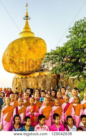 Kyaikhto Myanmar - January 10 2012: Young nuns under the delicately balanced golden Stupa on the sacred Buddhist mountain