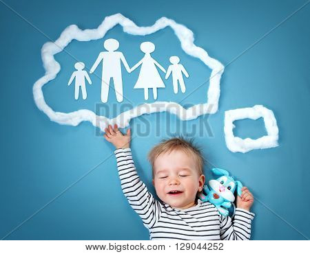 Little baby boy dreaming of a family on blue background