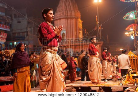 VARANASI, INDIA - JANUARY 3, 2013: Young indian priests Brahmins pray during the night ritual dedicated to the River Ganges on January 3, 2013. Varanasi urban agglomeration had a population of 1435113