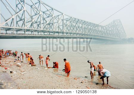 KOLKATA, INDIA - JAN 19, 2013: Many people bathing in river Hooghly under the busy Howrah bridge on January 19, 2013 in Calcutta. Howrah bridge bears 100000 vehicles and more than 150000 people every day