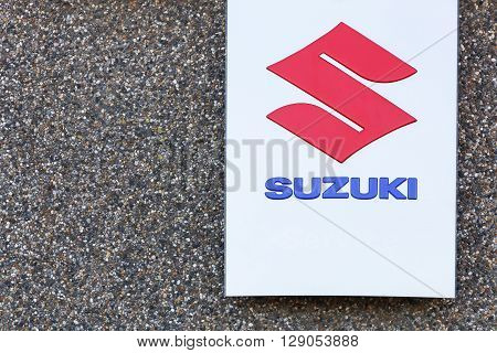 Skanderborg, Denmark - May 5, 2016: Suzuki logo on a wall. Suzuki is a Japanese multinational corporation headquartered in Japan which specializes in manufacturing automobiles, four-wheel drive vehicles, motorcycles, all-terrain vehicles