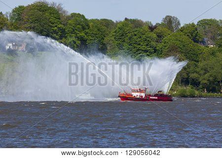 Hamburg, Germany - May 8, 2016: Fireboat spraying water during departure parade of 827th Hamburg Port anniversary